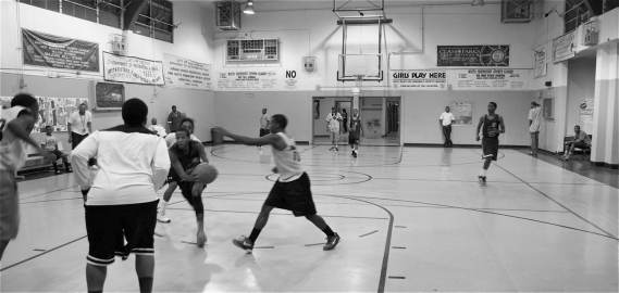 Young men play basketball during the Summer Night Lights program at the Jordan Downs rec center. It's one of the few opportunities for young men to be out late at night. Sahra Sulaiman/LA Streetsblog