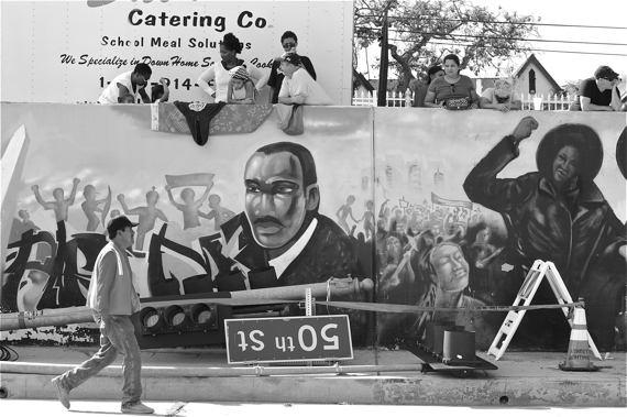 People gather above murals commemorating Black struggles along Crenshaw Blvd. to wait for the arrival of the Space Shuttle Endeavour. Sahra Sulaiman/Streetsblog L.A.