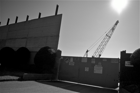 A crane peeks out from behind a makeshift wall recently put up by Freeport-McMoRan at the Murphy Drilling Site. Sahra Sulaiman/LA Streetsblog