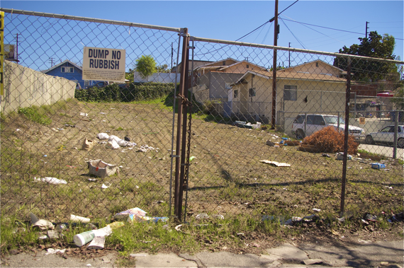 Trash accumulates in a vacant lot where dumping is discouraged by a sign. Sahra Sulaiman/LA Streetsblog