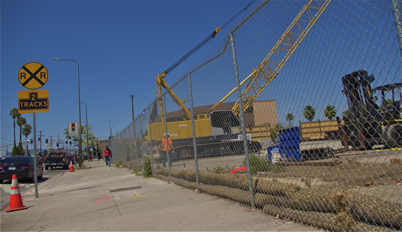 A boy walks past the staging area for the Crenshaw Line at Crenshaw and Exposition. Recently erected sound barriers can be seen along Exposition. Sahra Sulaiman/LA Streetsblog