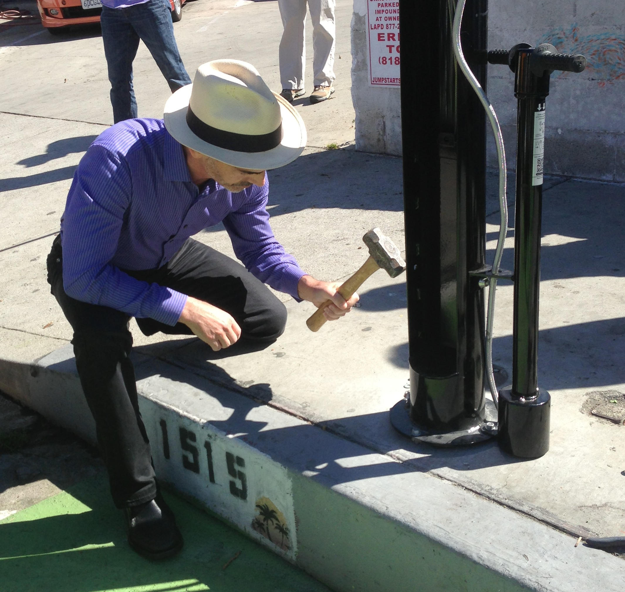 Councilmember Mitch O'Farrell hammers in the final pin to secure the new bike repair stand at Sunset Triangle Park Plaza
