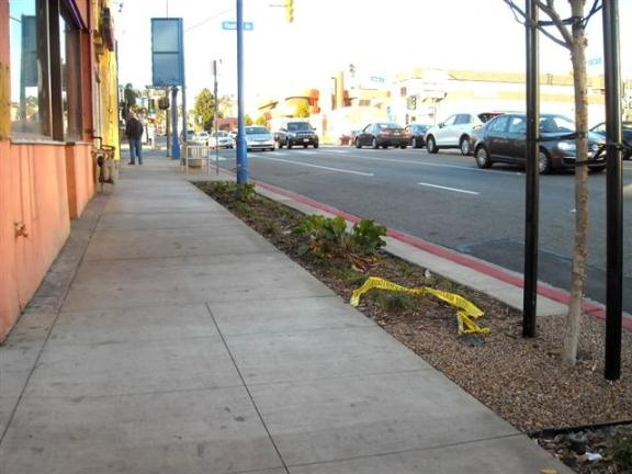 """La Brea Avenue, looking north: Same gloomy, non-descript concrete  sidewalks. Where is decorative pavement (that better attracts pedestrian life)? Where is a more  distinct buffer zone? This type of """"streetscape"""" is not too encouraging."""