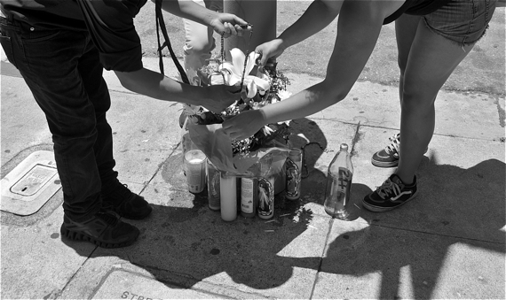 Friends lay rosaries on flowers at the memorial site for Oscar Toledo, Jr. Sahra Sulaiman/Streetsblog LA
