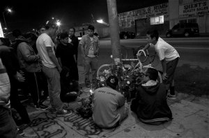 Friends of Oscar Toledo, Jr., gather around the ghost bike put up at 47th and Normandie in South LA. Sahra Sulaiman/Streetsblog LA. This photo is a finalist for an award from the L.A. Press Club