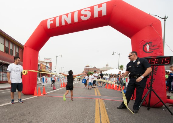 Run organizer Juan Romero and a police officer hold the tape for a speedy munchkin runner. Photo Eddie Ruvalcaba
