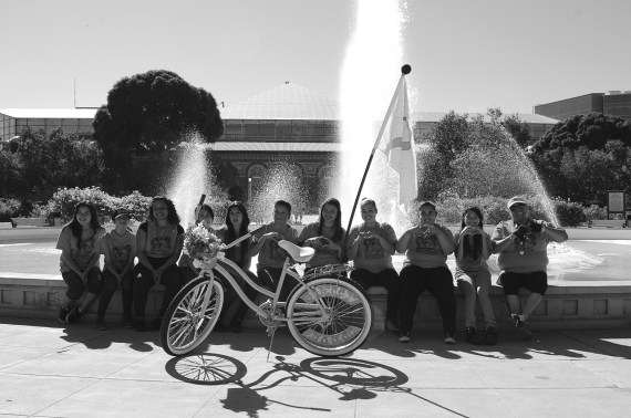 Members of the Sisterhood Pack (a subset within the club) take a break from the Cancer Awareness ride to pose with the bike they collaborated to build. The bike sports a flag listing the names of cancer victims from the community. Sahra Sulaiman/Streetsblog L.A.