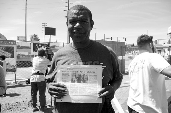 At yesterday's groundbreaking, South L.A. resident Dana Gilbert holds an L.A. Times article from 1992 about the plans to rebuild the vacant lots at Manchester and Vermont and the jobs the effort would bring to the area. The article features a photo of himself with then-Mayor Tom Bradley. Gilbert showed up to ask for the job he was promised 23 years ago. Sahra Sulaiman/Streetsblog L.A.