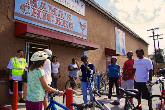 Riders on the healthy food tour gather in front of Mama's Chicken, a corner market that has undergone a conversion and now features some produce provided by CSU. Sahra Sulaiman/Streetsblog L.A.
