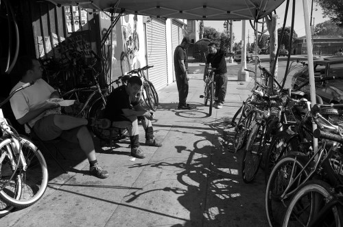 Santiago Galvez (hat), owner of Jesus' Bike Shop consults with a customer while youth who hang out at the shop and sometimes help out look on. Sahra Sulaiman/Streetsblog L.A.