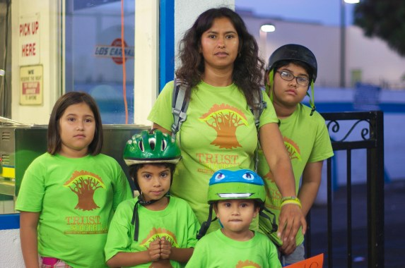 Maria Almeida stands with her children after the press conference. Her bike is outfitted with a saddle on the crossbar where her youngest child sits. Sahra Sulaiman/Streetsblog L.A.