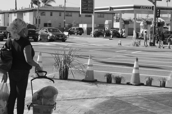 A woman eyes up the scramble crosswalk that could take her through the intersection much more efficiently than she could normally go--something that is appealing when you are carrying a lot of stuff with you. Sahra Sulaiman/Streetsblog L.A.