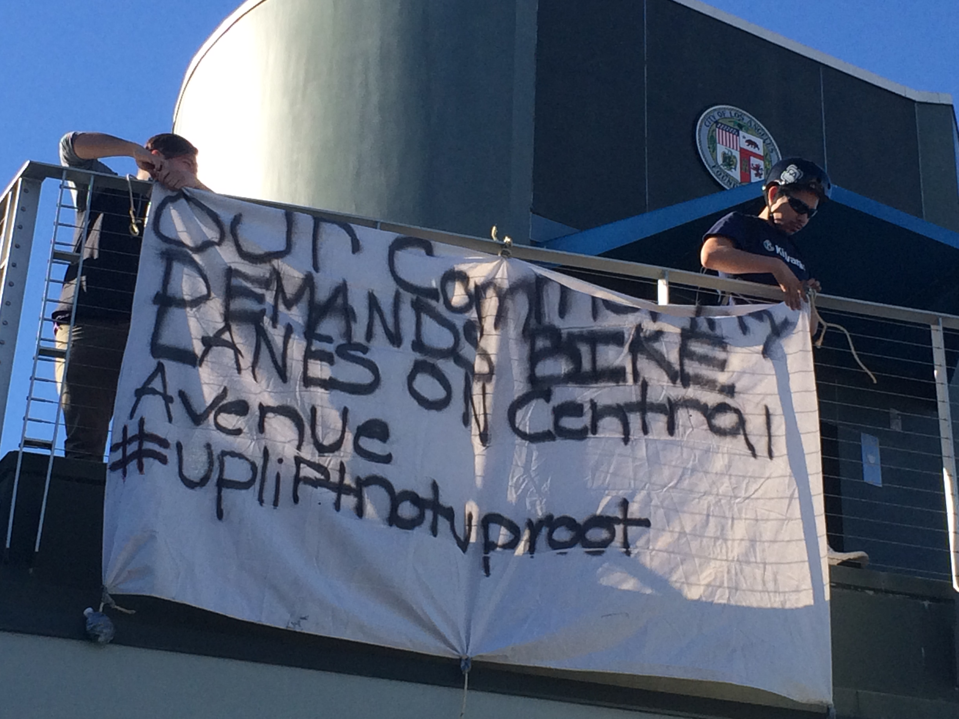 Members of TRUST South L.A. hang a banner from Curren Price's constituent center. Photo: Ashley Hansack