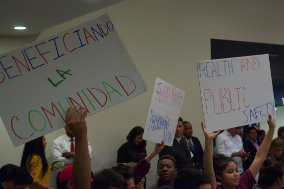Youth hold up signs matching talking points on the Reef's power point presentation. Sahra Sulaiman/Streetsblog L.A.