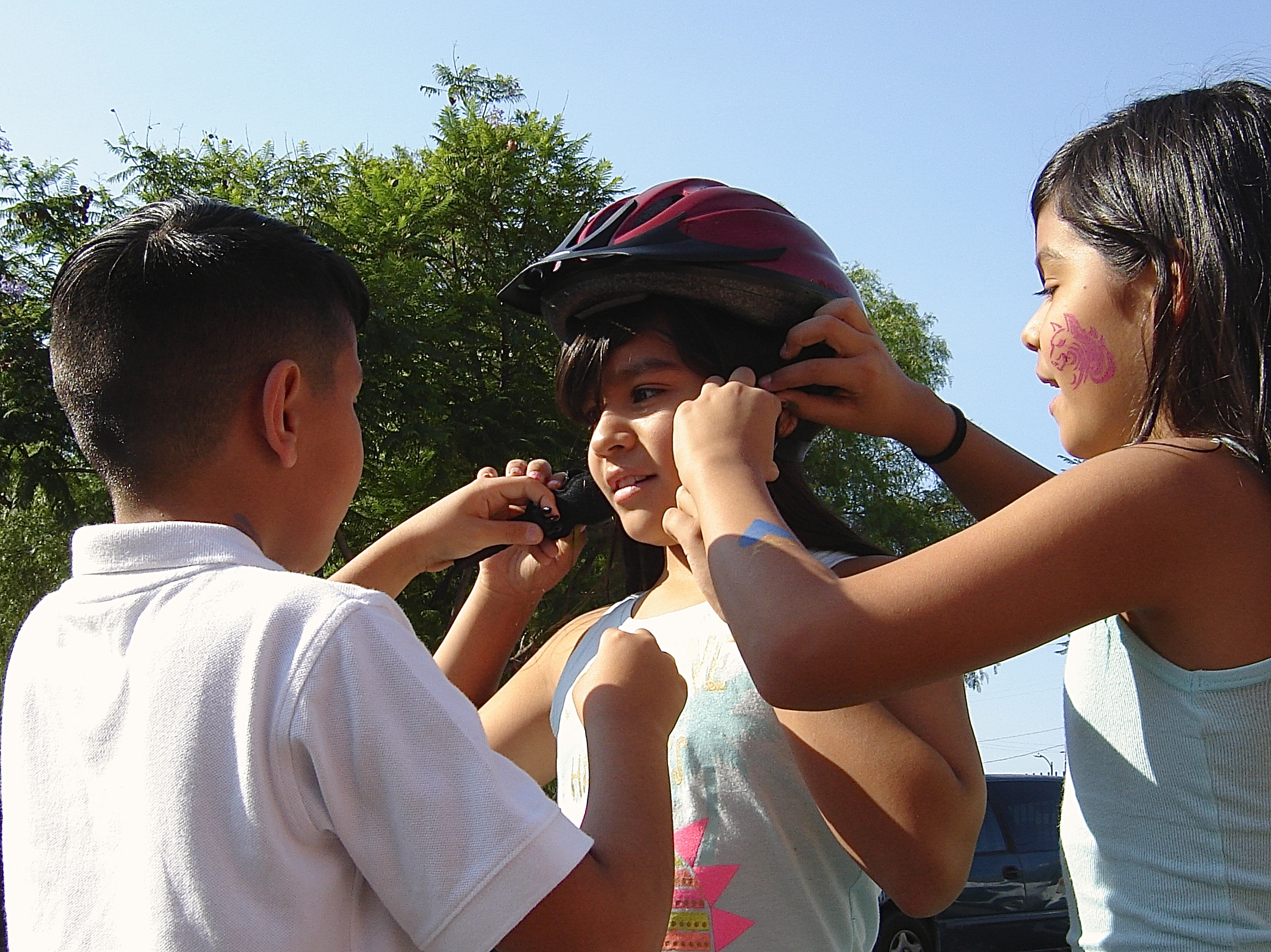 Kids practice putting on a helmet with tips they learned from Multicultural Communities for Mobility. Sahra Sulaiman/Streetsblog L.A.