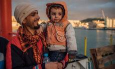 Isä ja poika odottavat laivan saapumista Italiaan öisen pelastusoperaation jälkeen.
