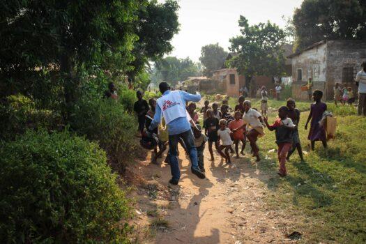 Mies tanssii yhdessä lasten kanssa. Miehellä on päällään liivi, jossa on Lääkärit Ilman Rajoja -järjestön logo.