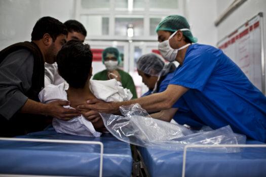 Hoitohenkilökunta nostaa potilasta sairaalasängyltä