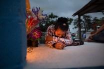 Una joven se postra ante la tumba de un familiar. Foto: Edu León.