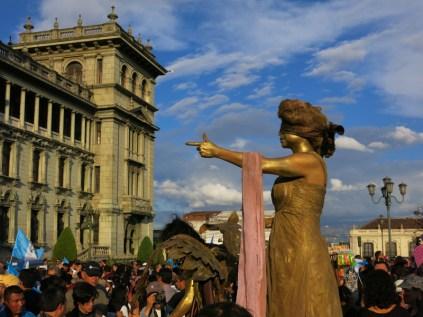 Un grupo de artistas callejeros representan estatuas durante la manifestación. La representación de la justicia, ciega, señala al Estado como responsable. En declaraciones sumamente torpes, Jimmy Morales, presidente de Guatemala, ha expresado su temor de denunciar esto como crimen de Estado.