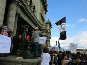 Un hombre agita una bandera de Guatemala en luto. A ese duelo nos sumamos los países de América Latina que sabemos que algo muy similar podría pasarnos. Compartimos la pobreza, su criminalización y las agresiones del Estado contra las mujeres.