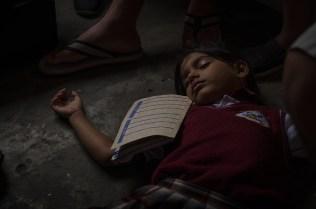 Rendida de cansancio, una niña duerme en el suelo aún con el uniforme de la escuela. Foto: Vicente Gaibor del Pino