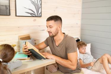Young father with open book reading story to his little daughter in bedroom