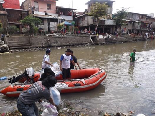 Warga menggunakan boat dari Save Our River mengangkat goni berisi tanah.