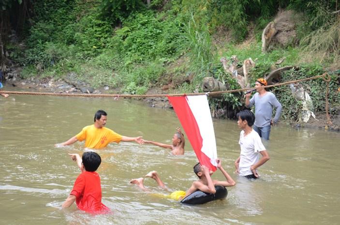 Seorang anak mencium bendera merah putih saat melewati garis finish lomba balap hanyut.