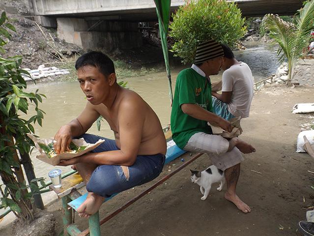 Warga makan siang di pinggi sungai