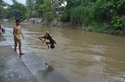 Seorang anak berakrobat dengan melompat ke Sungai Deli dengan gaya membelakangi sungai.