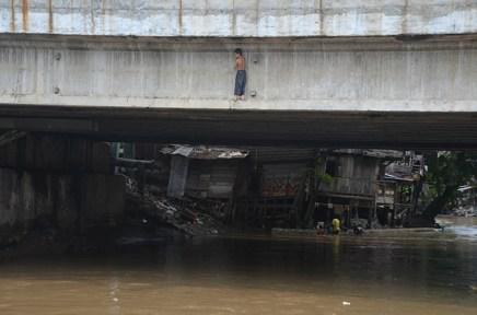 Seorang anak dengan kehati-hatian berdiri di pijakan sempit di bawah jembatan
