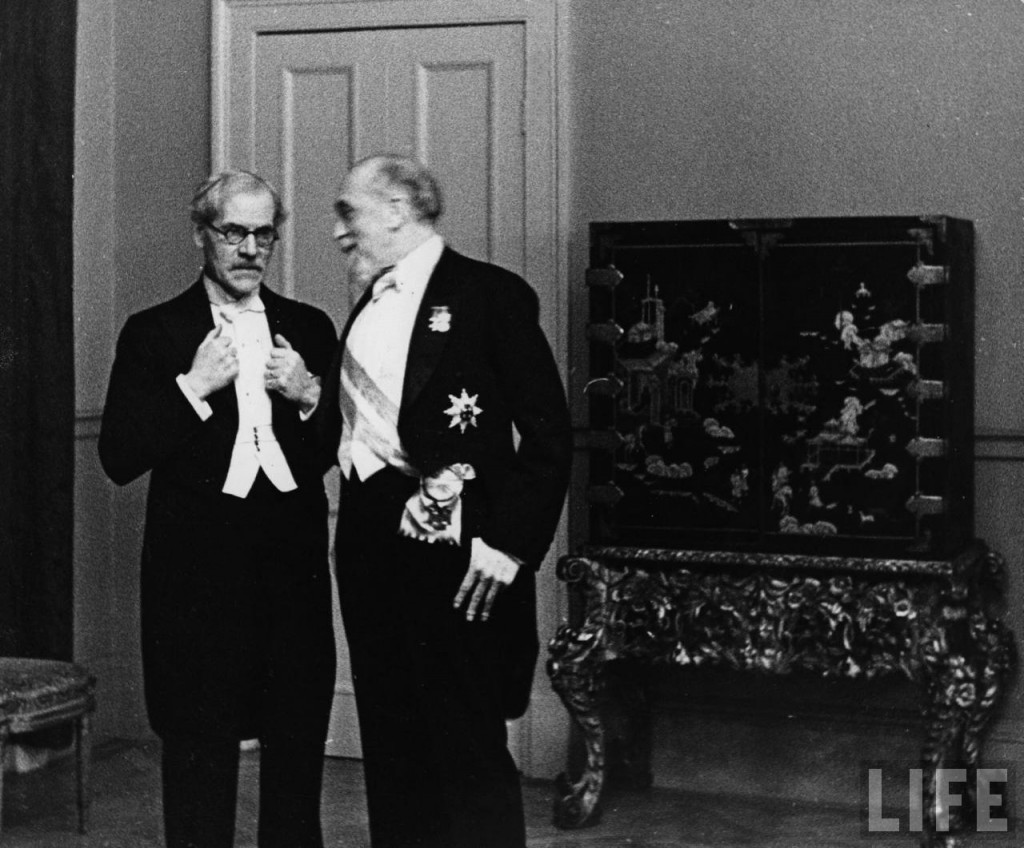 Governor of the bank of England, Montagu Norman talks to Ramsay Macdonald who has chosen, appropriately, to dress as an undertaker for the occasion