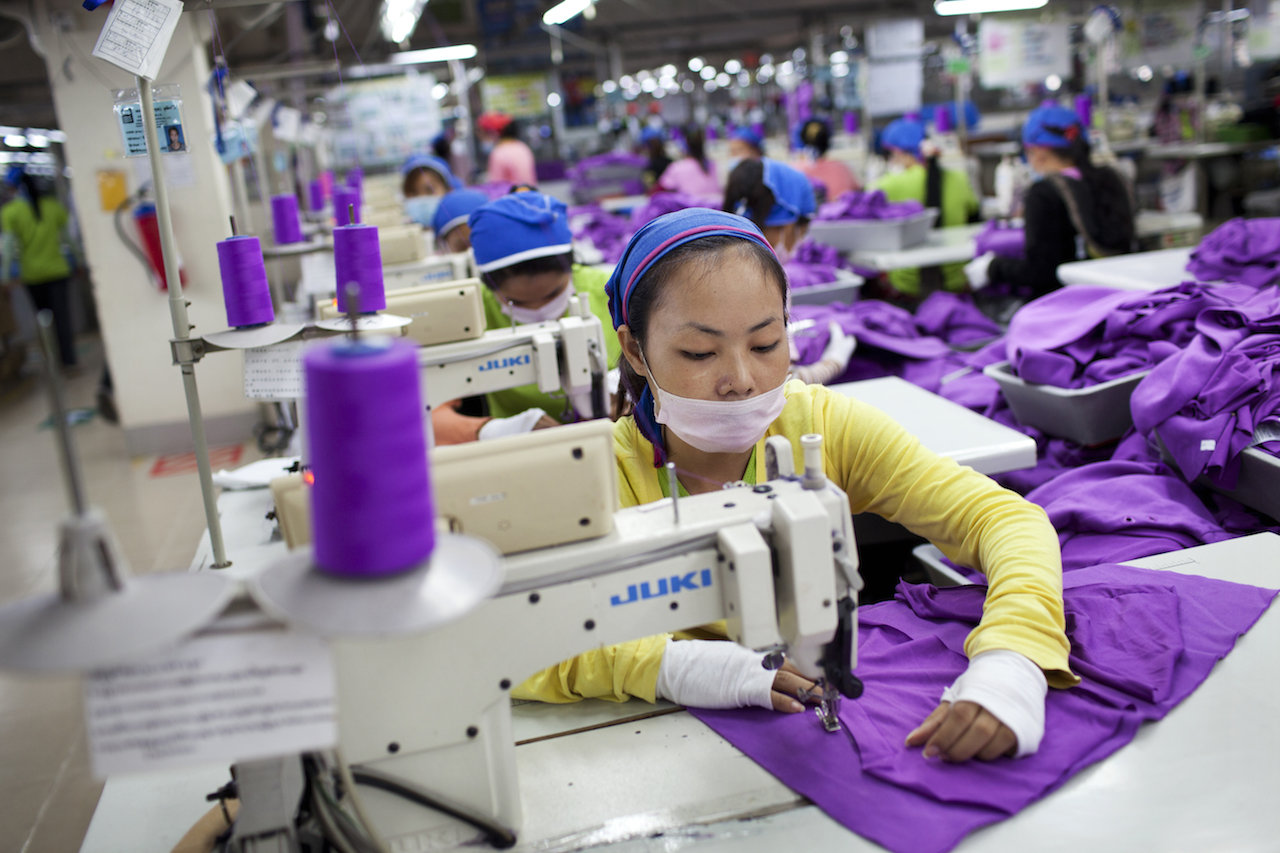 Hundreds of Asian women sewing purple material inside a factory (sweat shop)