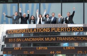 """""""Sin advertir sobre las consecuencias de la transacción, ese día los principales funcionarios financieros de la administración de Alejandro García Padilla, incluyendo a Melba Acosta, entonces secretaria del Departamento de Hacienda, y el presidente de la Junta del BGF, David Chafey, fueron fotografiados con sus lugartenientes en la sede de Morgan Stanley de Wall Street bajo un letrero que decía """"Felicidades Puerto Rico, $3.5 mil millones en """"Histórica Transacción de Bonos Municipales"""". Eran todo sonrisas y se chocaban las manos aludiendo a un gran triunfo"""" (Archivo)."""