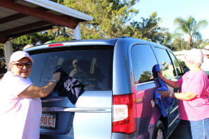 Pat Schmidt cleans a window on a car in the drying area - Pat is available to clean windows in anyone's home!