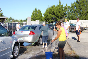 Some of the dedicated volunteers hard at work getting the grime off cars.