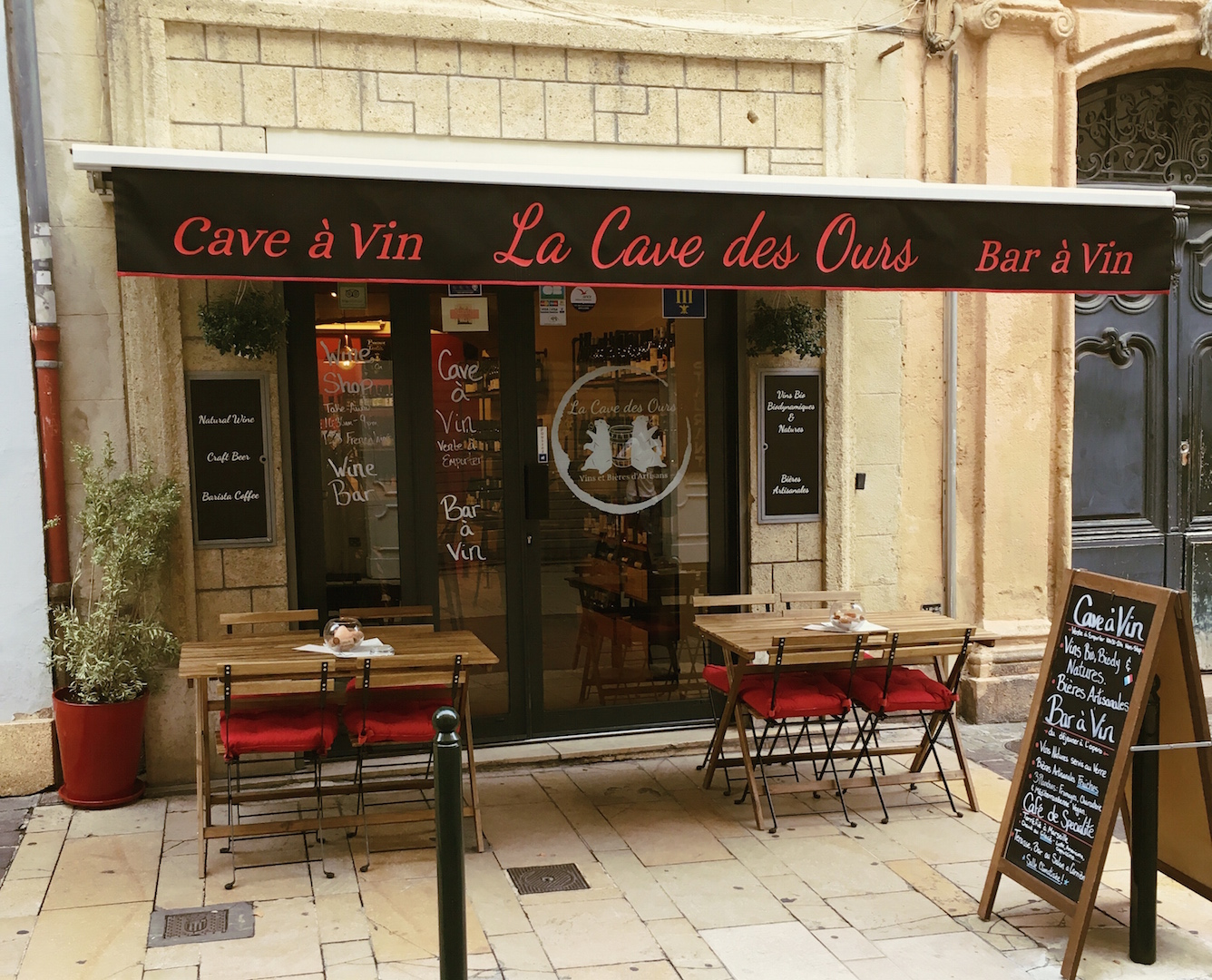 La Cave des Ours -Vins Naturels et Bières Artisanales - Aix-en-Provence- Exterior with side walk terrace, two wooden tables with four chairs each, red cushions, green plant in red pot, sandwich board display sign