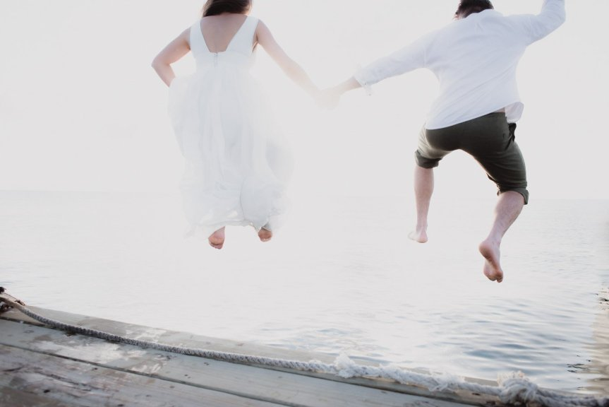 bride and groom jump into the ocean