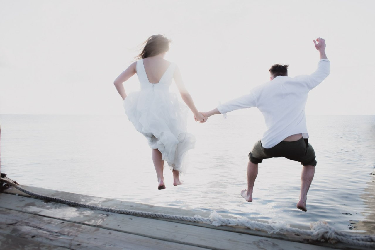 bride and groom jump into ocean with wedding dress gown