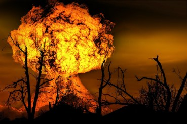 Image of a large orange and yellow blast with shadow of dead trees in foreground