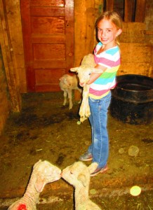 Raelyn with kissing lambs