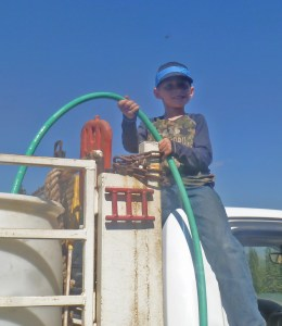 Seamus holding the hose for the water barrel