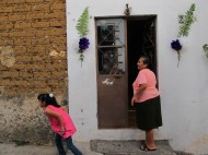 Rosita adorns the outside of her home for the barrios' celebration of Christ