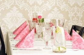 Teeman mukainen pinkki kattaus kahvipöydässä