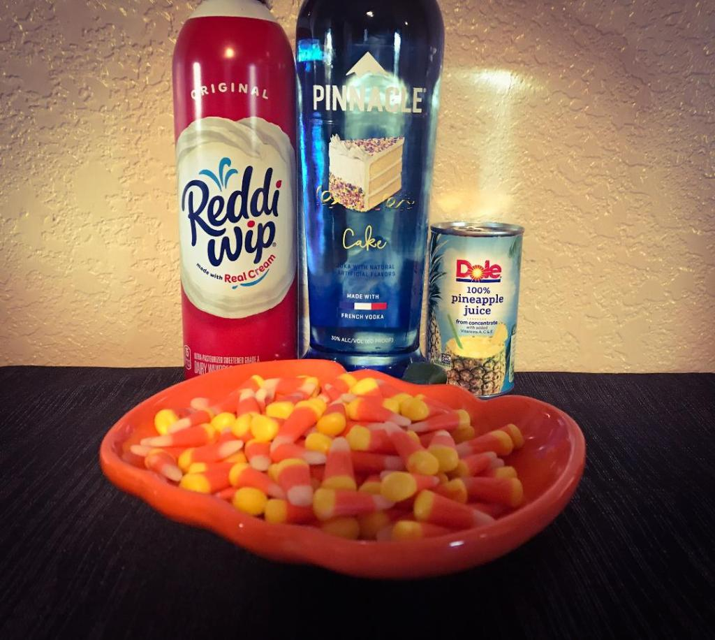 Ingredients to make Candy Corn Shot including: candy corn, Pinnacle Cake Vodka, pineapple juice, and whip cream.