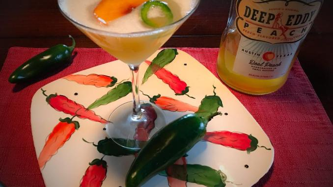 Spicy Peach Martini made with Deep Eddy Peach Vodka, Pineapple Juice, Lime Juice, Simple Syrup, Sliced Peaches and Jalapenos for garnish.