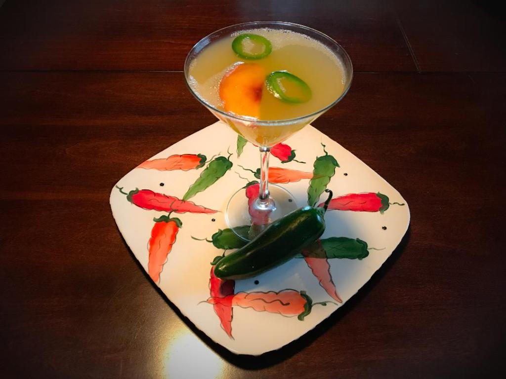 Spicy Peach Martini made with Deep Eddy Peach Vodka, Pineapple Juice, Lime Juice, Simple Syrup, Sliced Peaches and Jalapenos for garnish