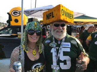 Green Bay Packers fans dressed up in Green Bay Packers clothes and tailgating before the game.
