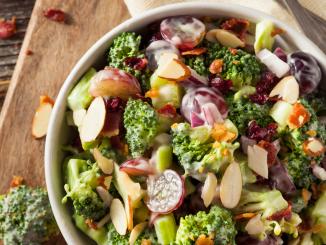 A creamy crunchy broccoli salad made with broccoli florets, crumbled bacon, chopped red onion, shredded cheddar cheese, cashews, grapes, craisins, mayo, white vinegar, & sugar.